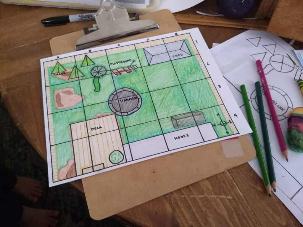 A Hand drawn grid map colored in with colored pencils on a clipboard with colored pencils laying next to it.
