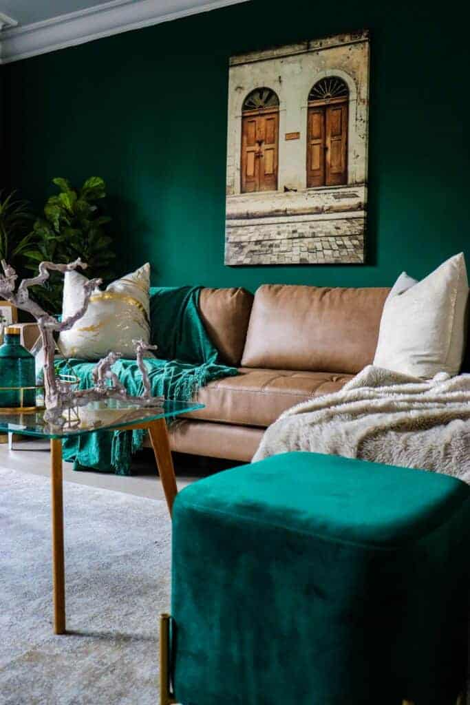 Dark Green room with beige couch and velvet footstool. Give a room new life with a dark coat of paint