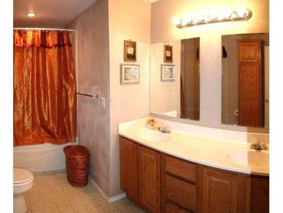 Master Bathroom with 90s style cabinetry and linoleum flooring