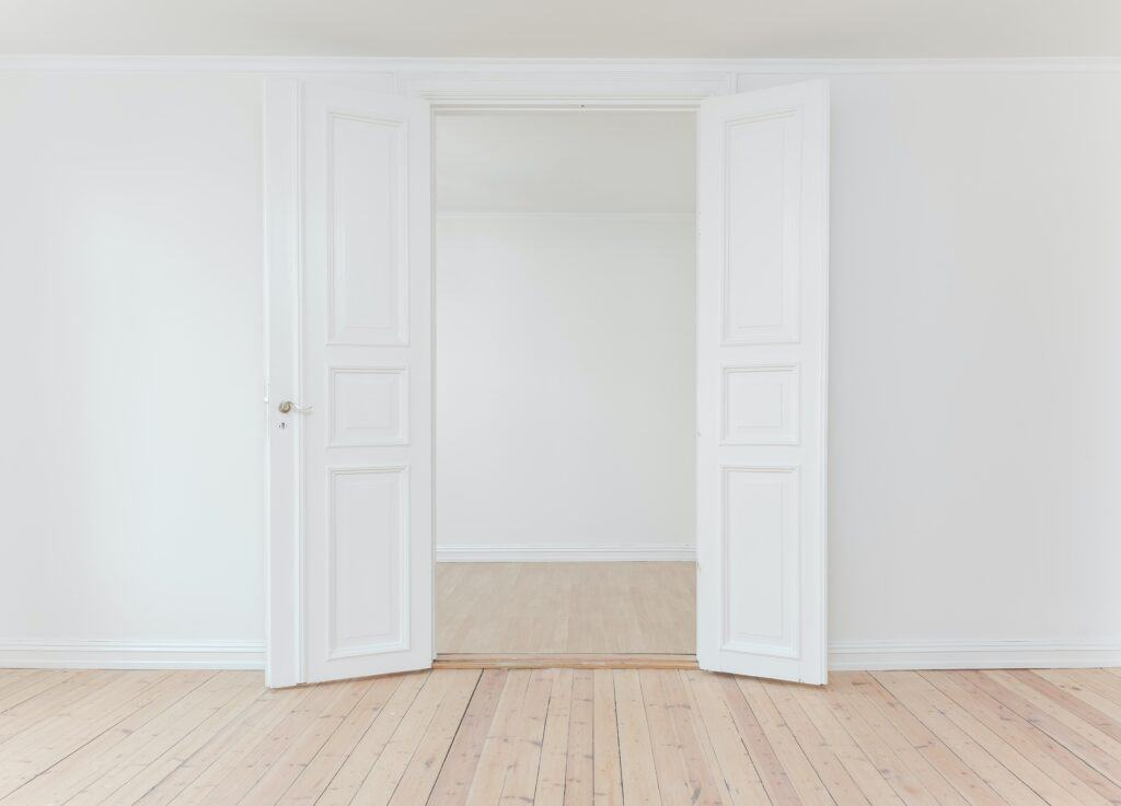 An empty room with white walls and hardwood floors, fresh clean room.