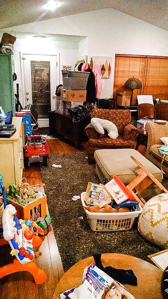 Living room and entryway cluttered with piles of toys and buckets of stuff before I downsized