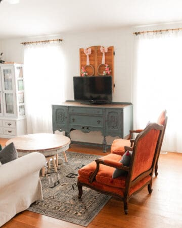 A brightly lit living room. Two orange velvet chairs, a cream colored couch, white bookcase, round wooden coffee table, and a blue vintage buffet. All surfaces cleaned and the room is completely decluttered and visually clean.