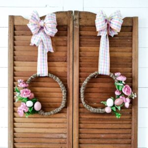 Two handmade spring wreaths with pastel pink and cream easter eggs and rose colored peonies. The wreaths are held up on two vintage wooden shutters with pink and blue ribbon.